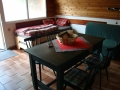 Jídelní stůl v přízemí a vzadu dvě stohovatelné postele a rozkládací pohovka